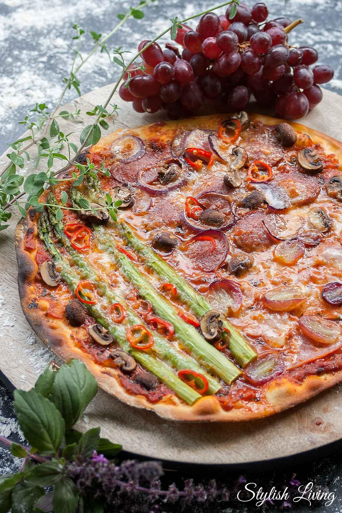 Pizza mit Salami, Schinken, Champignons, Weintrauben, Spargel