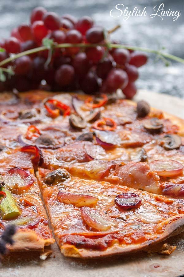 Pizza mit grünem Spargel, Schinken, Weintrauben, Salami