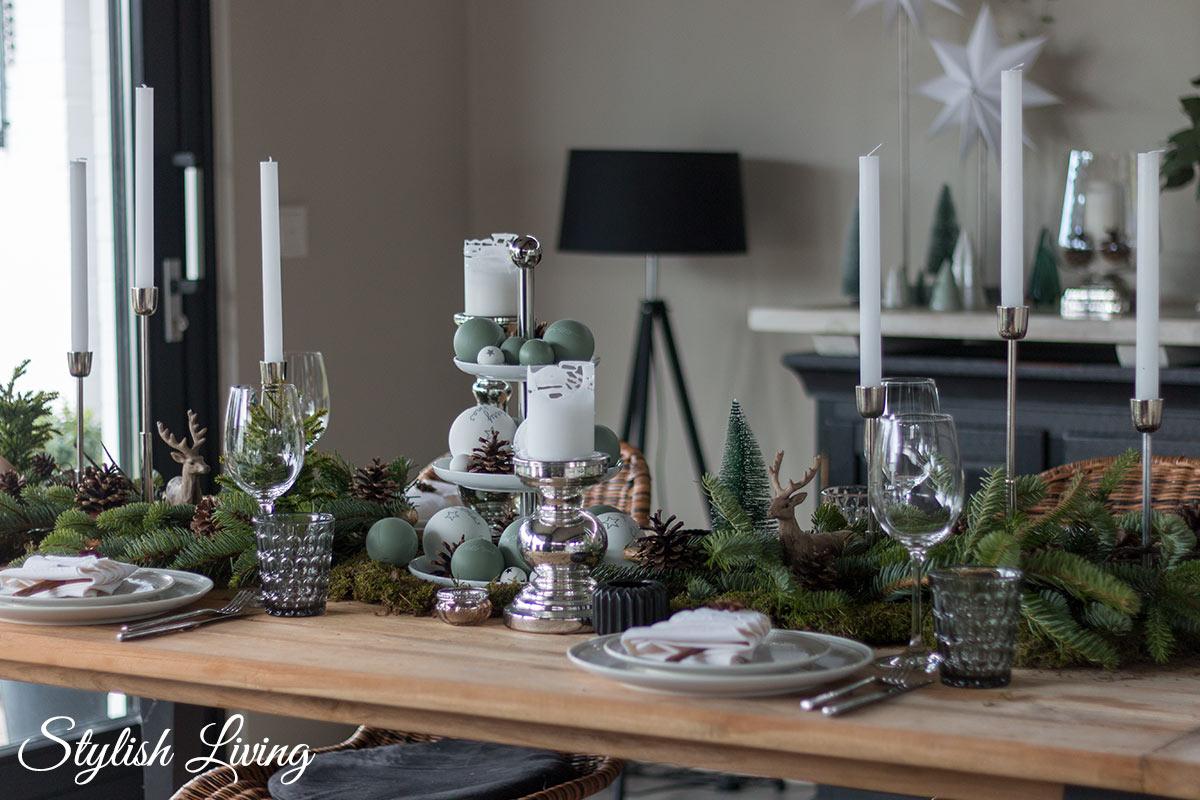 Weihnachtstischdeko mit Tanne, Zapfen, Moos und Weihnachtskugeln auf einer Etagere
