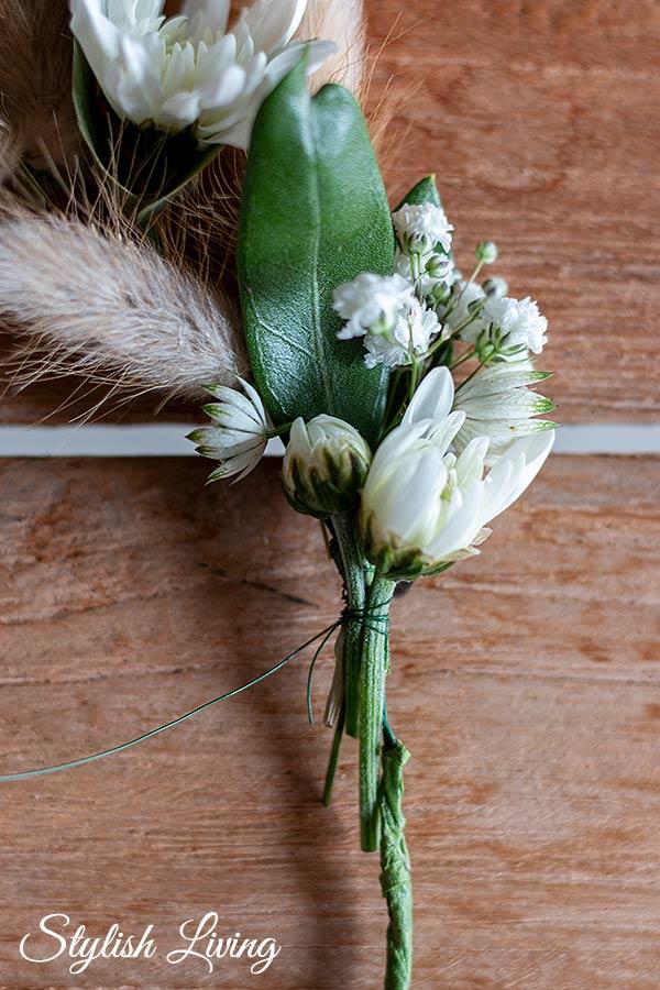 Die verschiedenen Blumen abwechseln entlang des Drahtkranzes mit Wickeldraht umwickeln