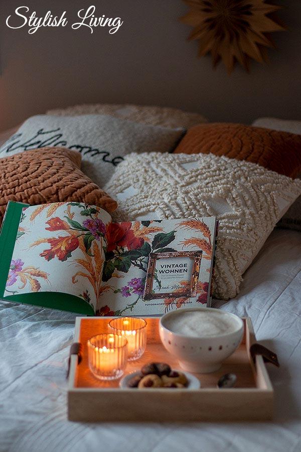 Gemütlichkeit im Schlafzimmer mit vielen Kissen, einem guten Buch und Kaffee oder Tee
